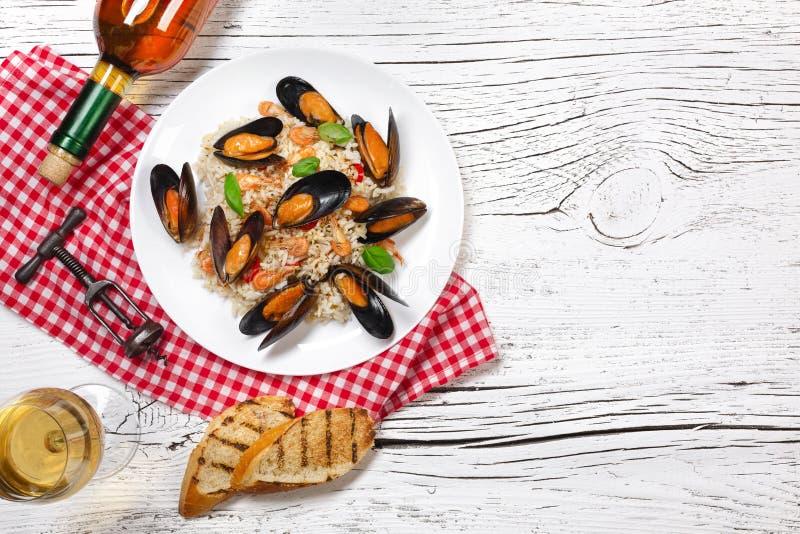 Τηγανισμένο ρύζι με τα μύδια, τις γαρίδες και το βασιλικό θαλασσινών σε ένα πιάτο με το μπουκάλι κρασιού, wineglass, την πετσέτα  στοκ φωτογραφία με δικαίωμα ελεύθερης χρήσης