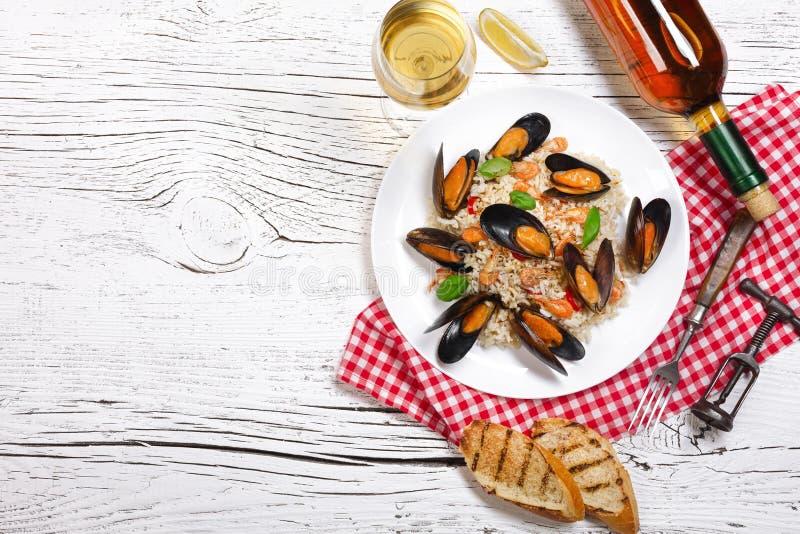 Τηγανισμένο ρύζι με τα μύδια, τις γαρίδες και το βασιλικό θαλασσινών σε ένα πιάτο με το μπουκάλι κρασιού, wineglass, την πετσέτα  στοκ εικόνες