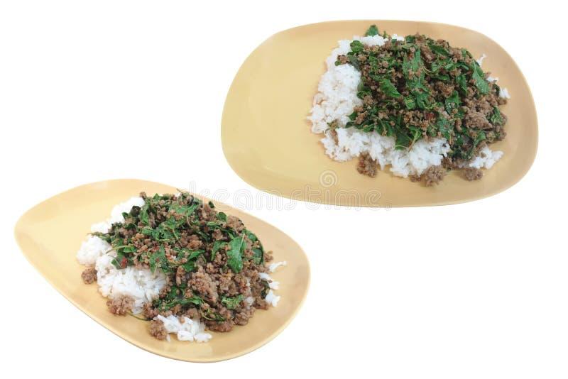 Τηγανισμένο ρύζι με το βασιλικό σε ένα πλαστικό κίτρινο πιάτο που απομονώνεται στο άσπρο υπόβαθρο με το ψαλίδισμα της πορείας στοκ εικόνα