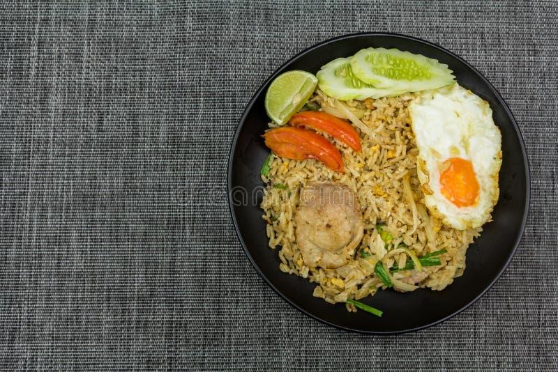 Τηγανισμένο ρύζι με το χοιρινό κρέας, τον ασβέστη, την πατάτα, τα αγγούρια και το τηγανισμένο αυγό στο β στοκ φωτογραφίες