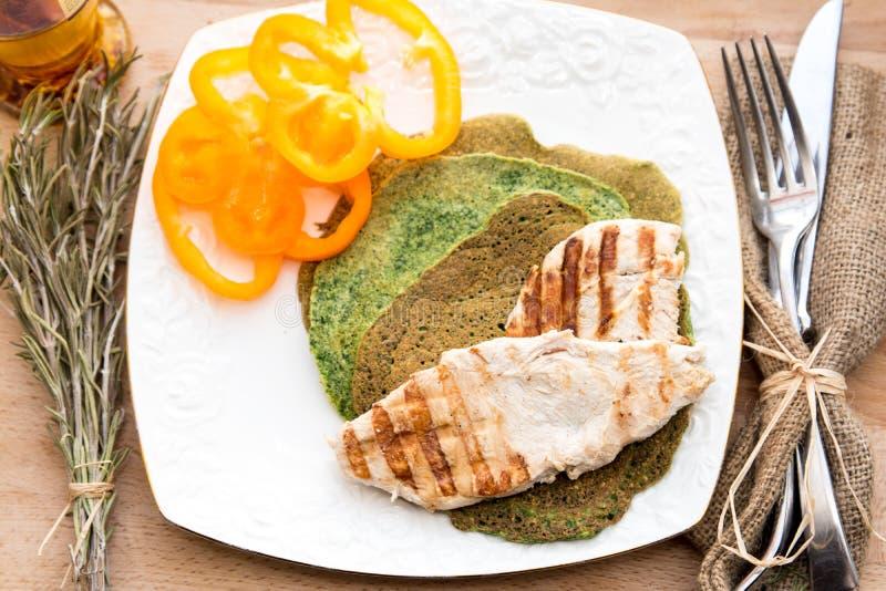 Τηγανισμένο στήθος κοτόπουλου με τις τηγανίτες σπανακιού και την κίτρινη πάπρικα στοκ φωτογραφία με δικαίωμα ελεύθερης χρήσης