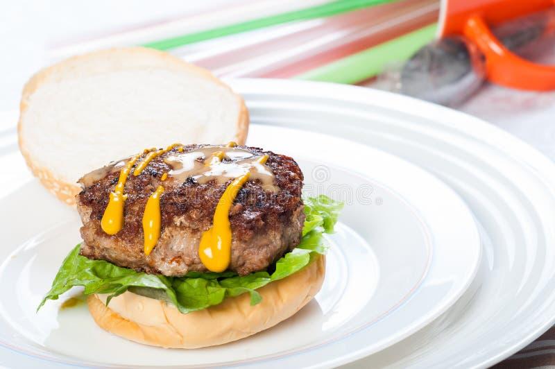 Τηγανισμένο τηγάνι burger με τις σάλτσες μουστάρδας και σουσαμιού στοκ εικόνες