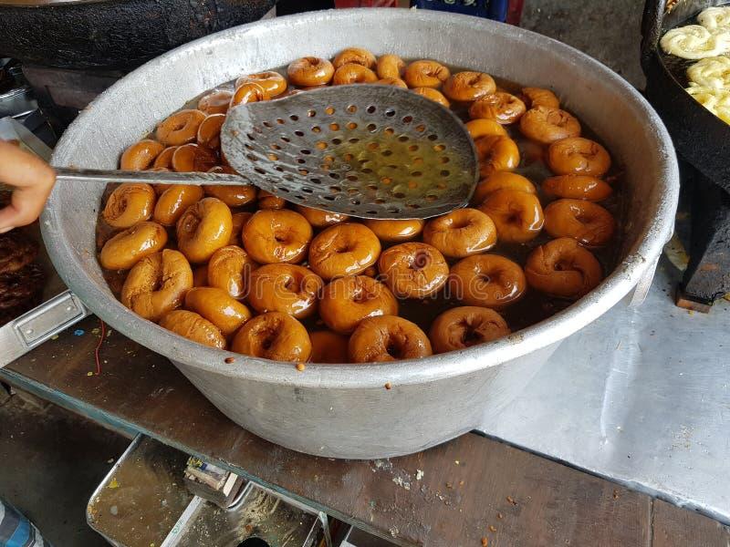 Τηγανισμένο vada τροφίμων που βυθίζεται στο γλυκό σιρόπι σε ένα μεγάλο εμπορευματοκιβώτιο αλουμινίου στοκ φωτογραφίες
