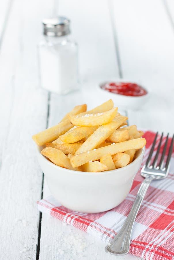 Τηγανιτές πατάτες σε ένα άσπρο κύπελλο στον πίνακα - επιλογές φραγμών ή γρήγορου φαγητού στοκ εικόνες