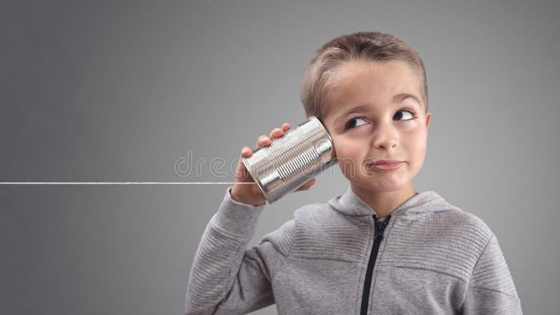 Τηλέφωνο δοχείων κασσίτερου που ακούει τις περίεργες καλές ειδήσεις στοκ φωτογραφία