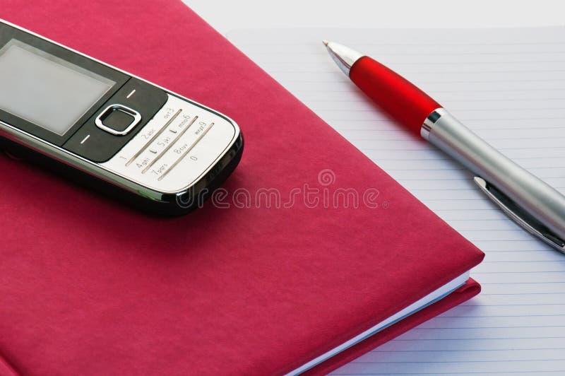 τηλέφωνο μολυβιών σημειωματάριων στοκ εικόνες
