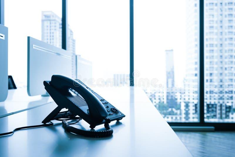 Τηλέφωνο στο γραφείο με τη μεγάλη άποψη πόλεων παραθύρων σύγχρονο γραφείο στοκ εικόνες
