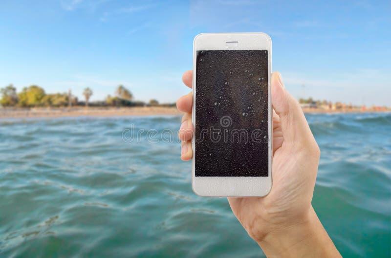 Τηλέφωνο υγρό στην παραλία στοκ εικόνες