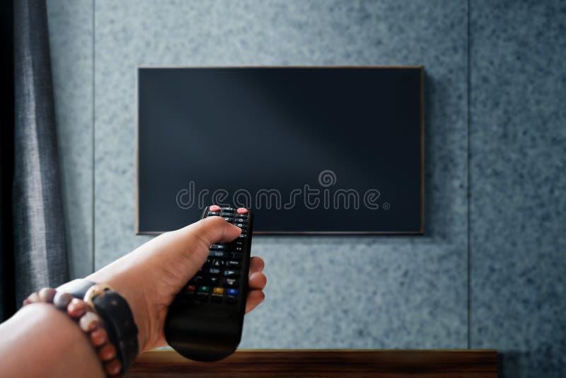 Τηλεοπτική έννοια προσοχής TV εκμετάλλευσης χεριών μακρινές στον έλεγχο ή το μεταβαλλόμενο κανάλι Χαλάρωση στο σύγχρονο καθιστικό στοκ εικόνες