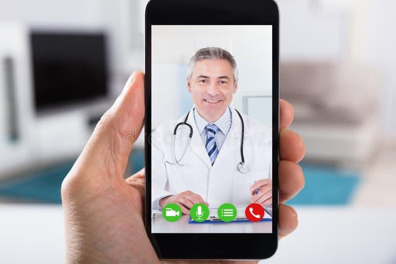 Τηλεοπτική σύσκεψη προσώπων με το γιατρό σε Smartphone στοκ φωτογραφίες