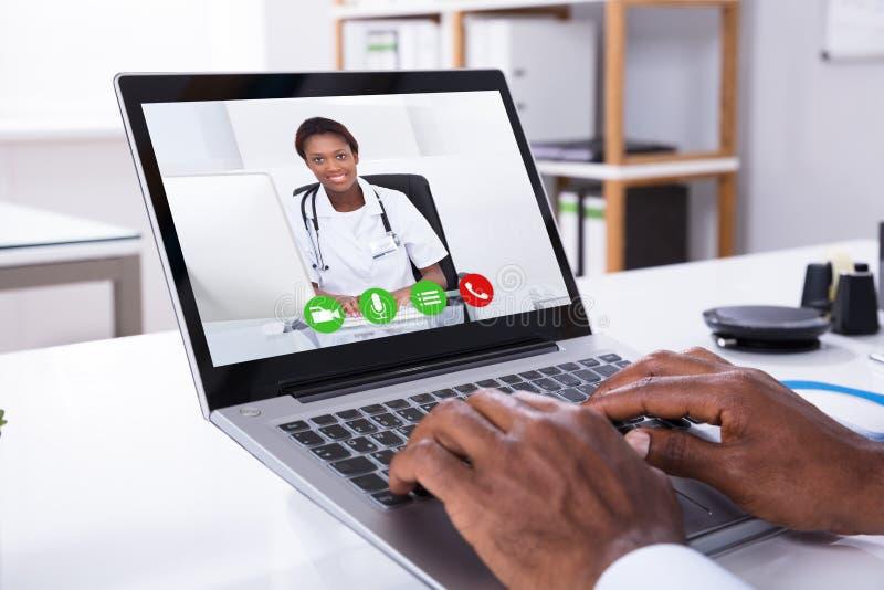 Τηλεοπτική σύσκεψη προσώπων με το θηλυκό γιατρό μέσω του lap-top στοκ φωτογραφίες με δικαίωμα ελεύθερης χρήσης