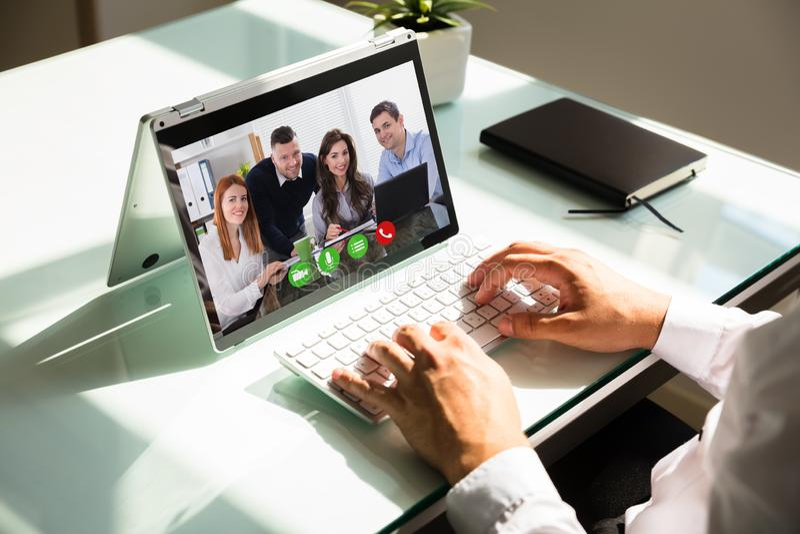 Τηλεοπτική σύσκεψη χεριών επιχειρηματία στο lap-top στοκ φωτογραφίες