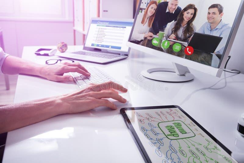 Τηλεοπτική σύσκεψη Businessperson με τους συνεργάτες στον υπολογιστή στοκ φωτογραφίες