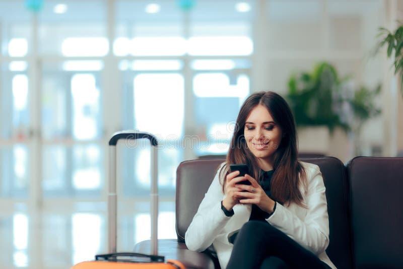 Τηλεφωνικά μηνύματα ανάγνωσης γυναικών στη αίθουσα αναμονής αερολιμένων στοκ εικόνα με δικαίωμα ελεύθερης χρήσης
