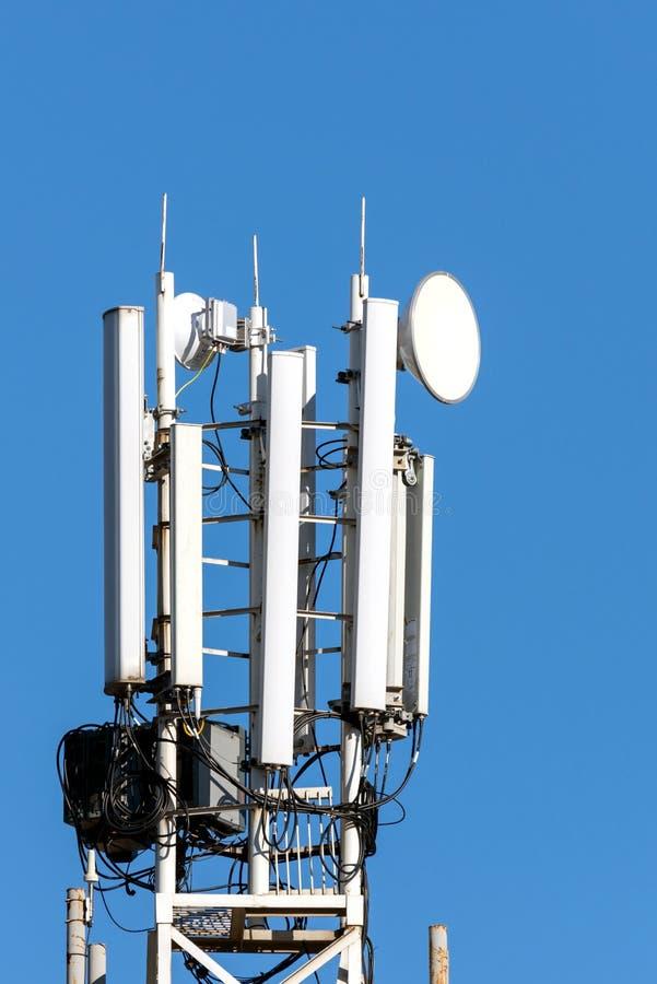 Τηλεφωνικός πύργος κυττάρων επικοινωνίας στο υπόβαθρο μπλε ουρανού στοκ εικόνες