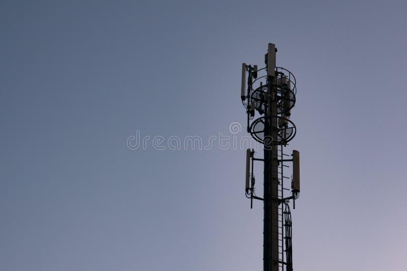 Τηλεφωνικός πύργος κυττάρων/κεραία ή ιστός επικοινωνιών στη σκιαγραφία στο σούρουπο ενάντια στο σκούρο μπλε ουρανό στοκ εικόνες