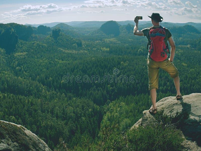 Τηλεφωνικός φωτογράφος Ο τουρίστας στην άκρη παίρνει τις τηλεφωνικές εικόνες στοκ εικόνες