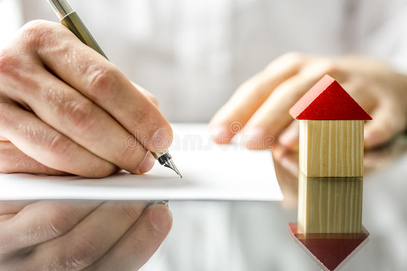 Την άτομο που υπογράφει μια σύμβαση κατά αγορά ενός καινούργιου σπιτιού στοκ φωτογραφία με δικαίωμα ελεύθερης χρήσης
