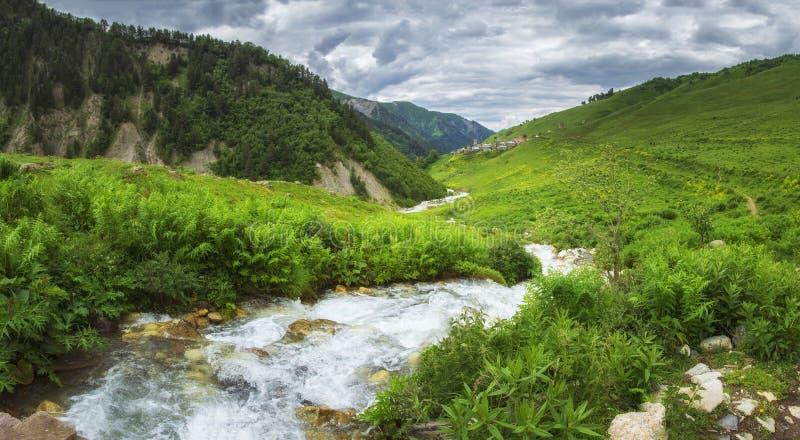 Της Γεωργίας τοπίο φύσης στην περιοχή Svaneti με τον ποταμό βουνών στις ορεινές περιοχές Πράσινοι λόφοι και βουνά που καλύπτονται στοκ εικόνες