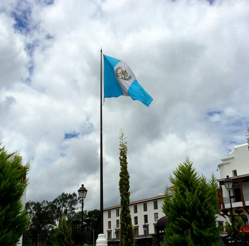Της Γουατεμάλας σημαία κάτω από έναν μπλε ουρανό σε Paseo Cayalà ¡ στοκ εικόνες