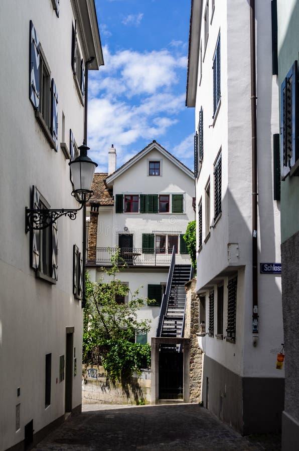 Της Ζυρίχης άσπρος τοίχος αλεών πόλεων παλαιός και στενός που χτίζει τον ηλιόλουστο μπλε ουρανό ημέρας στοκ εικόνα με δικαίωμα ελεύθερης χρήσης
