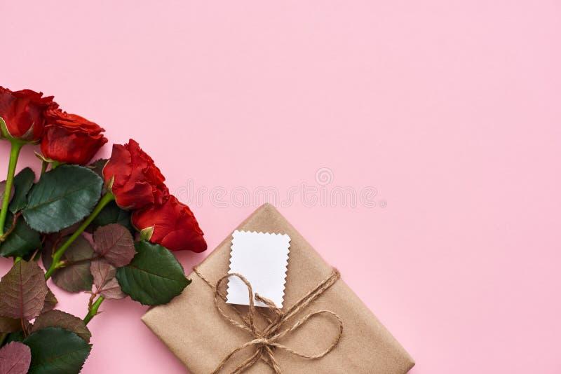 Της παρουσιάστε όλη αγάπη σας Ανθοδέσμη των φρέσκων κόκκινων τριαντάφυλλων και του μικρού κιβωτίου δώρων στοκ εικόνα