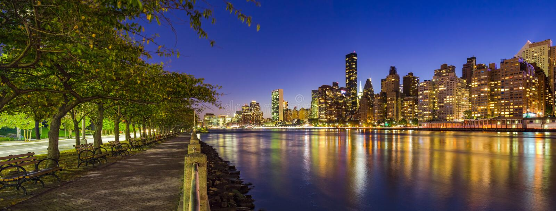 Της περιφέρειας του κέντρου ουρανοξύστες του Μανχάταν και ο ανατολικός ποταμός στο λυκόφως από τον περίπατο νησιών Roosevelt το κ στοκ φωτογραφία με δικαίωμα ελεύθερης χρήσης