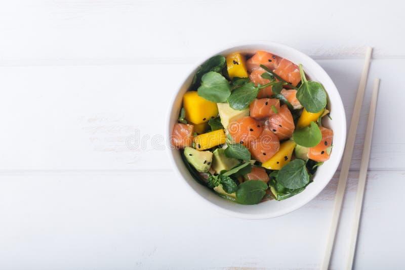 Της Χαβάης σαλάτα σπρωξίματος με το σολομό, το αβοκάντο και τα λαχανικά σε ένα κύπελλο σε ένα άσπρο ξύλινο αγροτικό υπόβαθρο με τ στοκ φωτογραφία με δικαίωμα ελεύθερης χρήσης