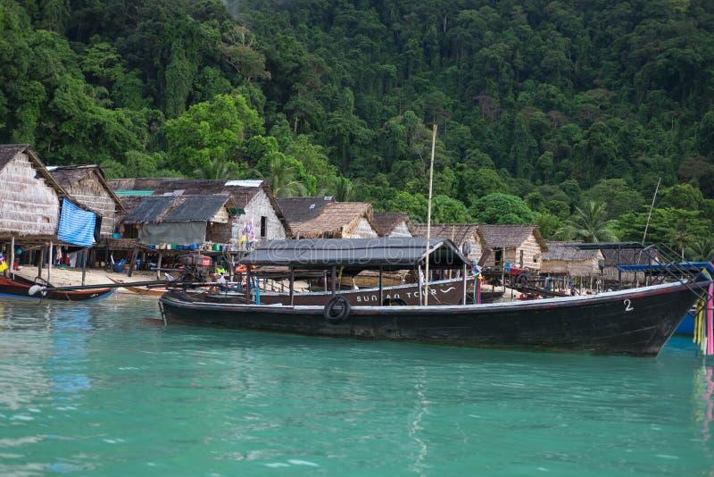Τη βάρκα Longtail που σταθμεύουν στη θάλασσα έχει το παλαιά χωριό και το δάσος στο υποστήριγμα στοκ φωτογραφία με δικαίωμα ελεύθερης χρήσης