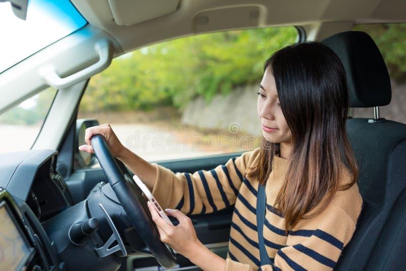 Τη γυναίκα που ψάχνει τη θέση κατά οδήγηση ενός αυτοκινήτου στοκ φωτογραφία