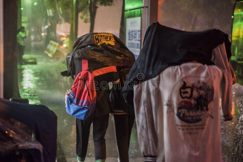 Τη νύχτα, μια ξαφνική νεροποντή, τρεις σπουδαστές Γυμνασίων χρησιμοποίησε τις κορυφές τους για να εμποδίσει τα κεφάλια τους και π στοκ φωτογραφία