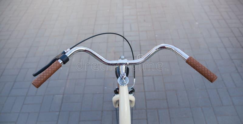 Τιμόνι ενός μπεζ ποδηλάτου με τις καφετιές λαβές στοκ φωτογραφία