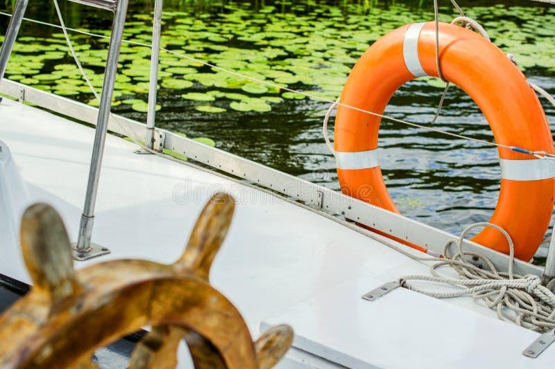 Τιμόνι και σημαντήρας ζωής σε ένα σκάφος στοκ εικόνες