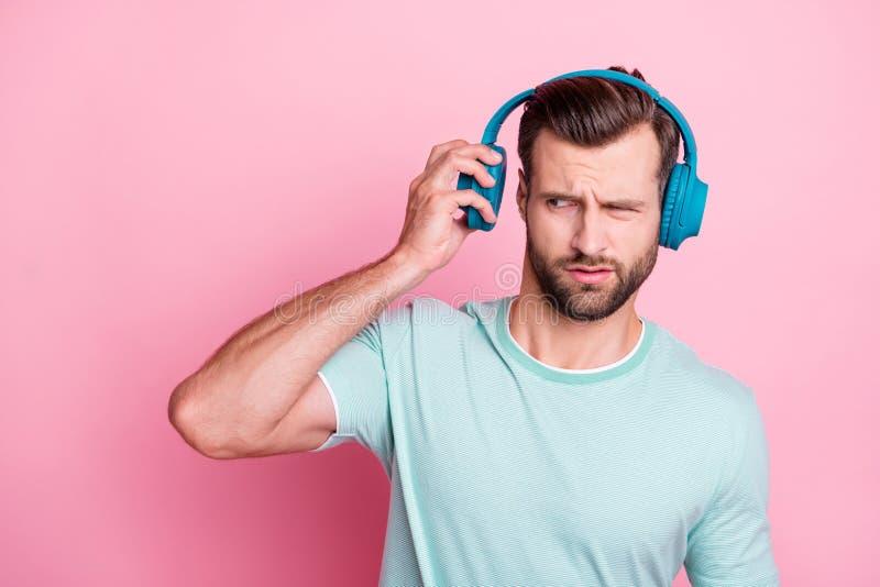 Τι είναι; Ο απογοητευμένος μουσικός εραστής αντιπαθεί το τραγούδι της λίστας που ακούει από το μπλε μοντέρνο ακουστικό νιώθει μπε στοκ εικόνες
