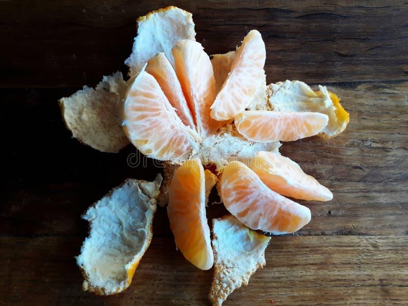 Τμήματα των ξεφλουδισμένων φρούτων μανταρινιών στον ξύλινο πίνακα στοκ εικόνες
