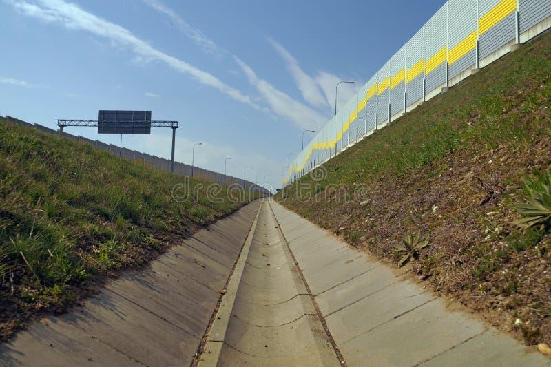 Τοίχος από τον ήχο - απορροφώντας επιτροπές Μια τάφρος που στραγγίζει την εθνική οδό στοκ φωτογραφία με δικαίωμα ελεύθερης χρήσης