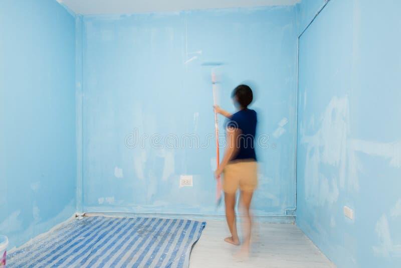 Τοίχος ζωγραφικής γυναικών θαμπάδων κινήσεων στο μπλε στοκ εικόνα με δικαίωμα ελεύθερης χρήσης