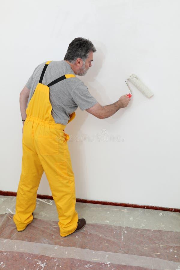 Τοίχος ζωγραφικής εργαζομένων στο δωμάτιο στοκ φωτογραφία με δικαίωμα ελεύθερης χρήσης