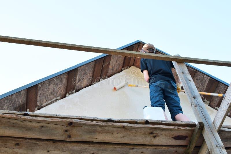Τοίχος ζωγραφικής νεαρών άνδρων του σπιτιού στοκ φωτογραφίες