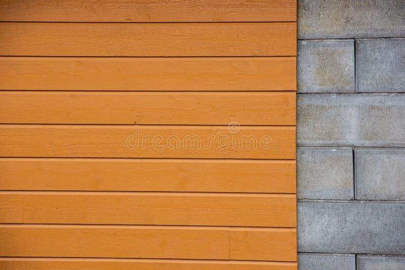 Τοίχος με τους φραγμούς τσιμέντου μερών, κίτρινη ξύλινη ξυλεπένδυση μερών στοκ εικόνα με δικαίωμα ελεύθερης χρήσης
