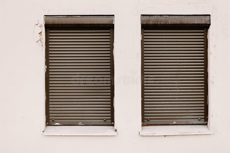 Τοίχος με δύο από τα κύλινδρος-τυφλά παράθυρα που κλείνει στοκ εικόνα