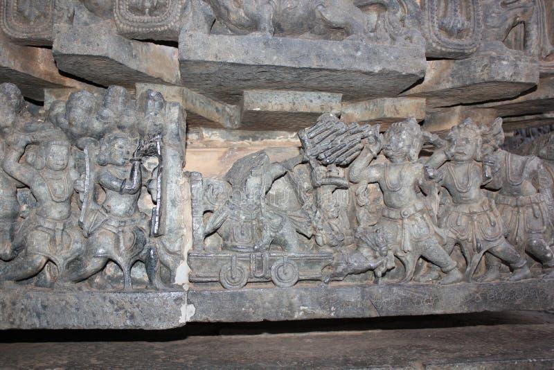 Τοίχος ναών Hoysaleshwara που χαράζει απεικονίζοντας την αρχαία πολεμική σκηνή όπου στρατιώτες που χρησιμοποιούν τα βέλη και το τ στοκ φωτογραφία