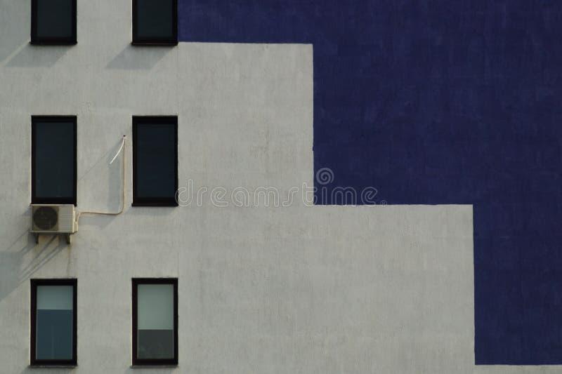 Τοίχος πολυόροφων κτιρίων στα πορφυρά και άσπρα χρώματα με το εδαφοβελτιωτικό και τα παράθυρα στοκ εικόνες