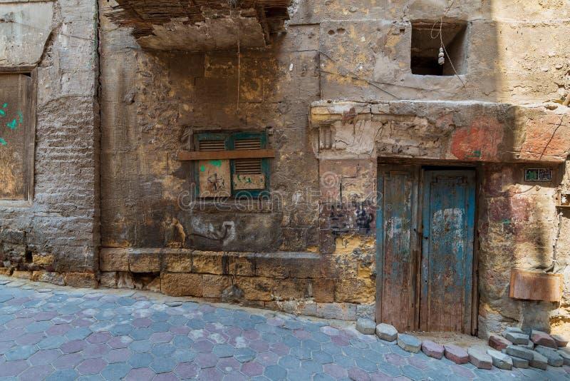 Τοίχος τούβλων πετρών Grunge με τη σπασμένη ξύλινη πόρτα και κλειστό σπασμένο παράθυρο στην εγκαταλειμμένη περιοχή στοκ εικόνες με δικαίωμα ελεύθερης χρήσης