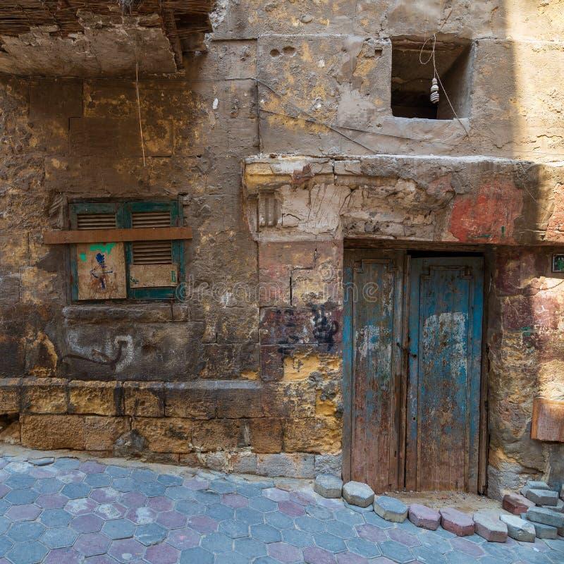 Τοίχος τούβλων πετρών Grunge με τη σπασμένη ξύλινη πόρτα και κλειστό σπασμένο παράθυρο στην εγκαταλειμμένη περιοχή στοκ εικόνες