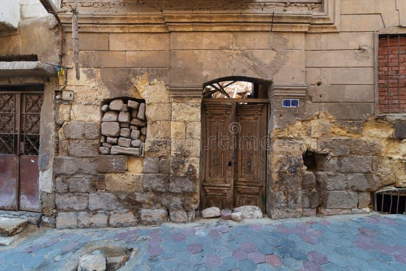 Τοίχος τούβλων πετρών Grunge με τη σπασμένη ξύλινη πόρτα και κλειστό σπασμένο παράθυρο στην εγκαταλειμμένη περιοχή στοκ φωτογραφία