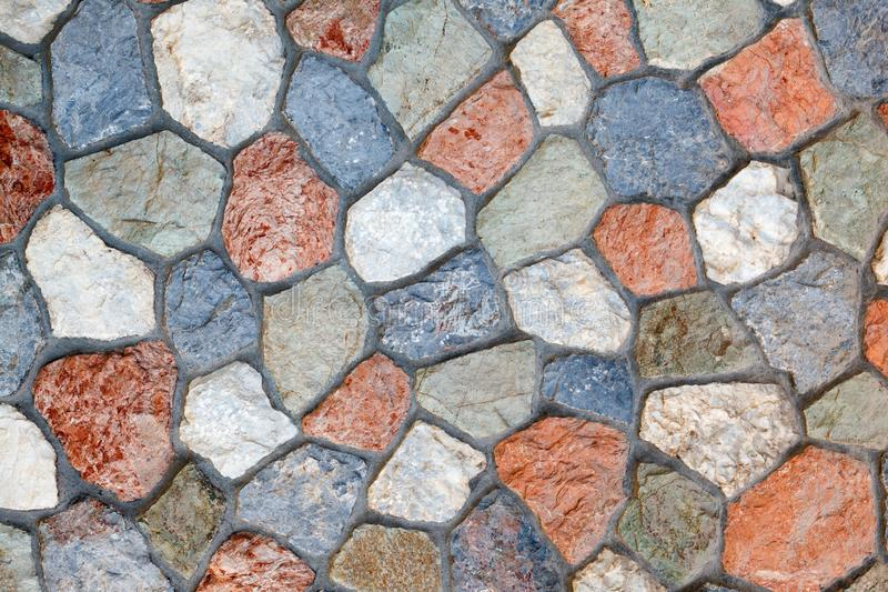 Τοίχος φιαγμένος από φυσική πολύχρωμη πέτρα της ανώμαλης μορφής που συνδέεται με το τσιμέντο στοκ φωτογραφία με δικαίωμα ελεύθερης χρήσης