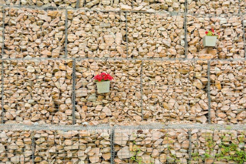 Τοίχος φρακτών Gabion από το πλέγμα χάλυβα με διακοσμημένα τα πέτρες λουλούδια στοκ φωτογραφία με δικαίωμα ελεύθερης χρήσης