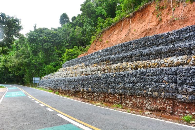 Τοίχος Gabion φιαγμένος από πέτρες στο πλέγμα χάλυβα, που χρησιμοποιείται ως φράκτης σε μια κλίση για την καθίζηση εδάφους προστα στοκ εικόνες