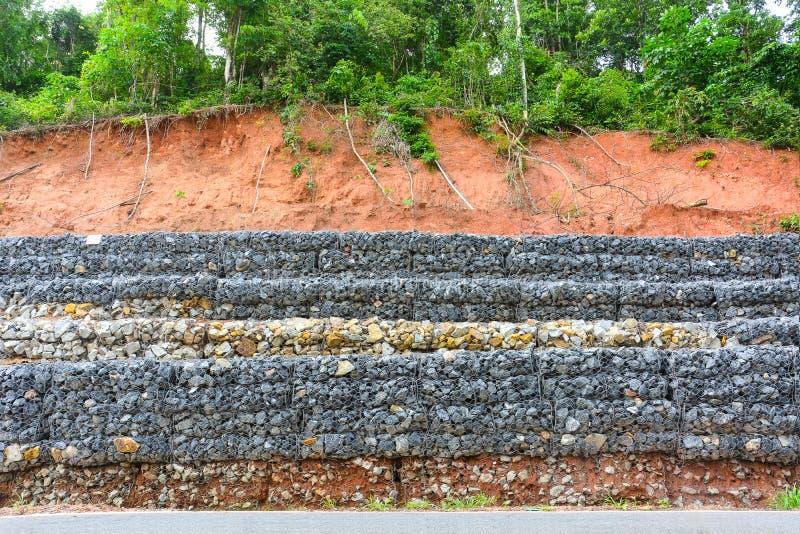 Τοίχος Gabion φιαγμένος από πέτρες στο πλέγμα χάλυβα, που χρησιμοποιείται ως φράκτης σε μια κλίση για την καθίζηση εδάφους προστα στοκ φωτογραφία με δικαίωμα ελεύθερης χρήσης